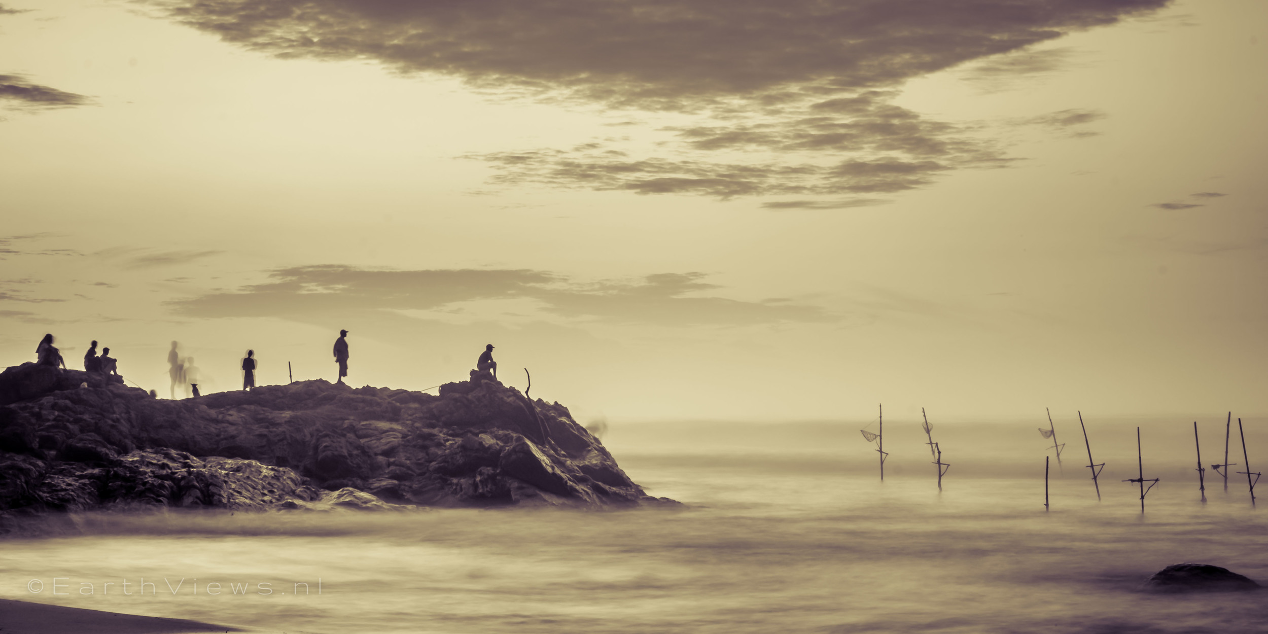 A (closer) shot of the people on the rocks on the beach of Weligama, Sri Lanka.