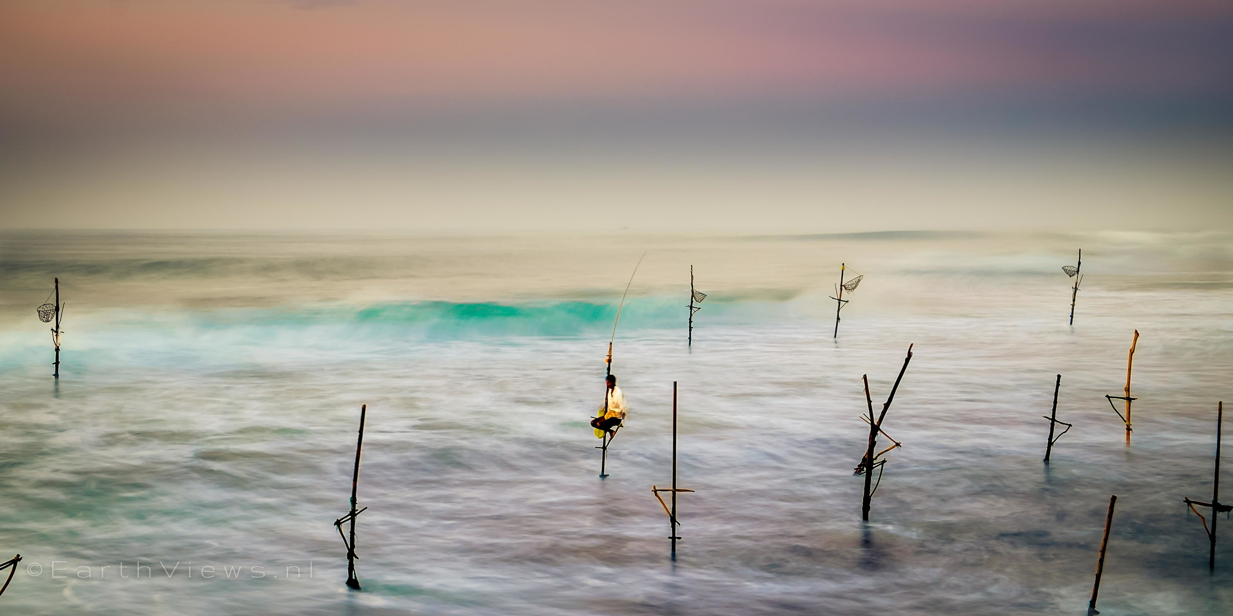 Stilt fishermen at the beach of Weligama, Sri Lanka.