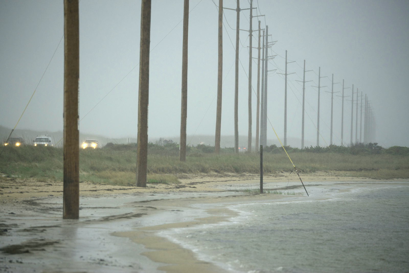 Receding shoreline threaten utility poles and Highway 12 near Avon, North Carolina, at the Haulover Day Use Area of the Cape Hatteras National Seashore.