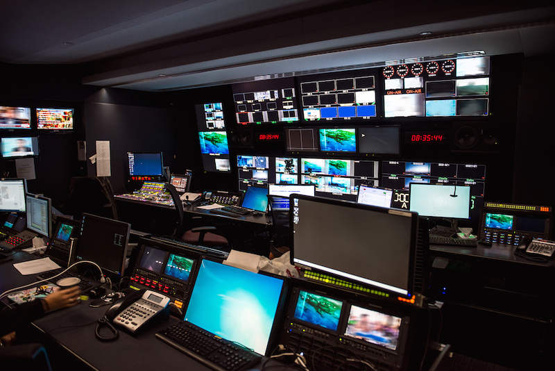 TV Broadcast news studio with many computer screens and control panels for live air broadcast.