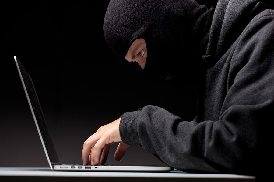 Computer hacker in a balaclava working in the darkness stealing