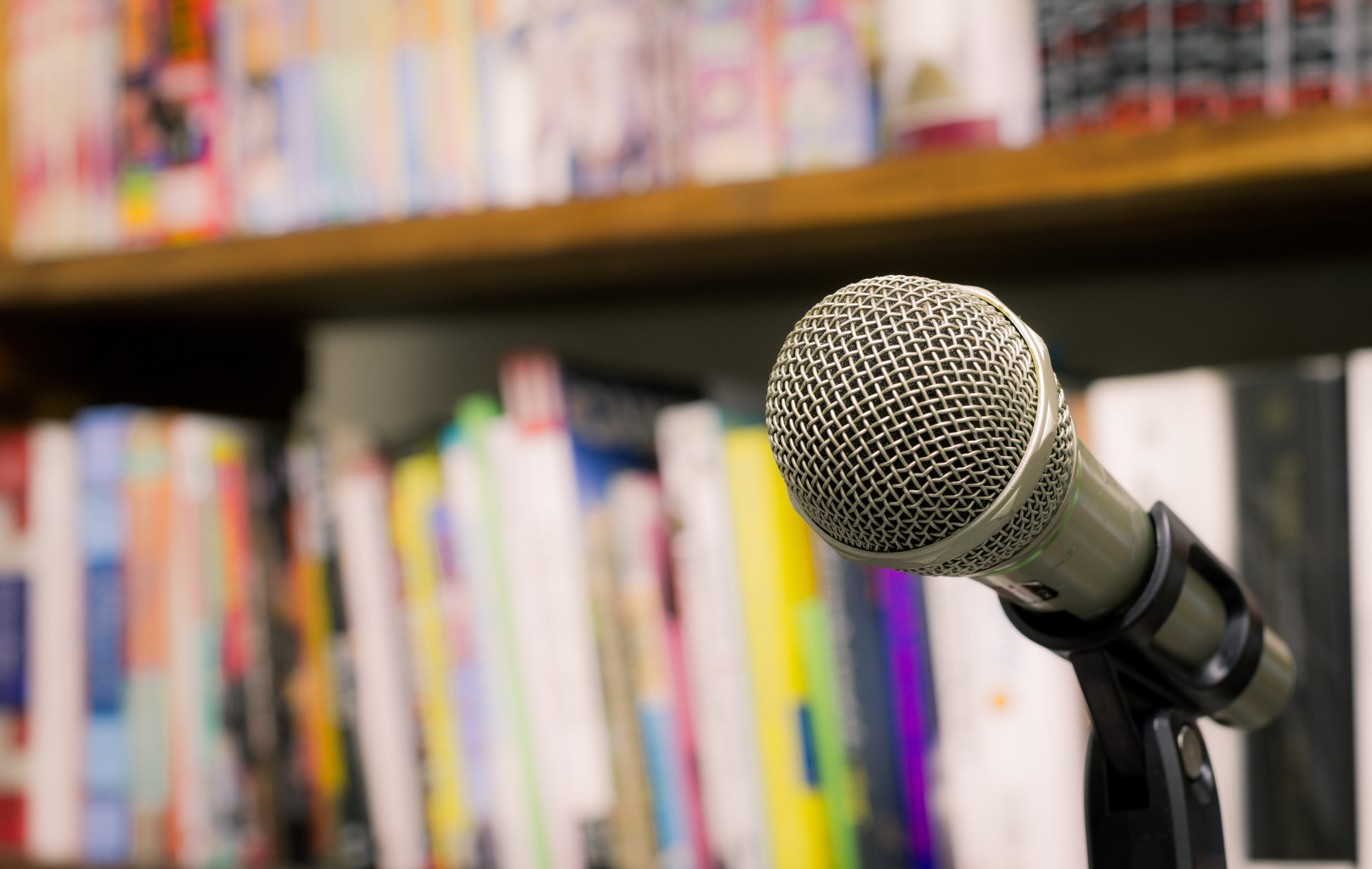 Microphone On The Background Of Blurred Bookshelf  In Library. S