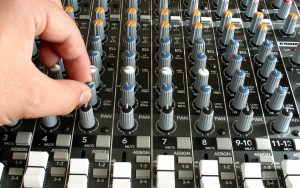 a picture of someone adjusting 80Hz on a Mackie Analog Mixing Desk
