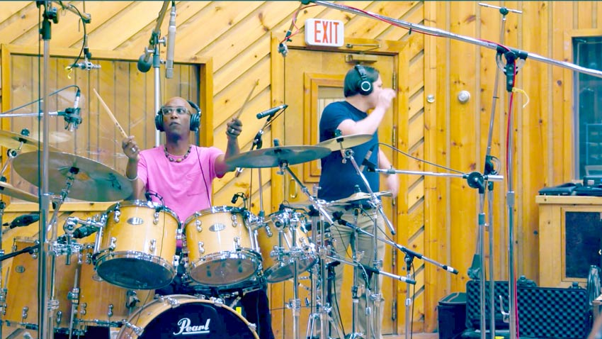 Look at where Omar Hakim's overheads are. Definitely either side of an axis running through the kick and snare.