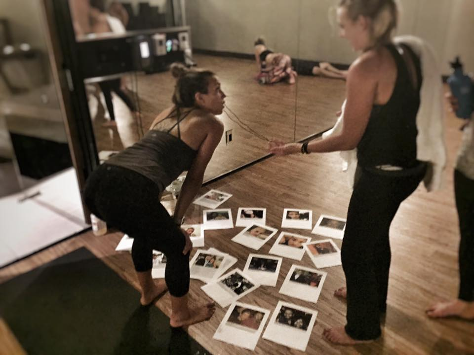 """Katie Burke talks with one of her students after a yoga session that was themed """"Love Over Fear."""" It was a way to remember the victims - whose photos are shown on the floor -of the Orlando nightclub shooting."""