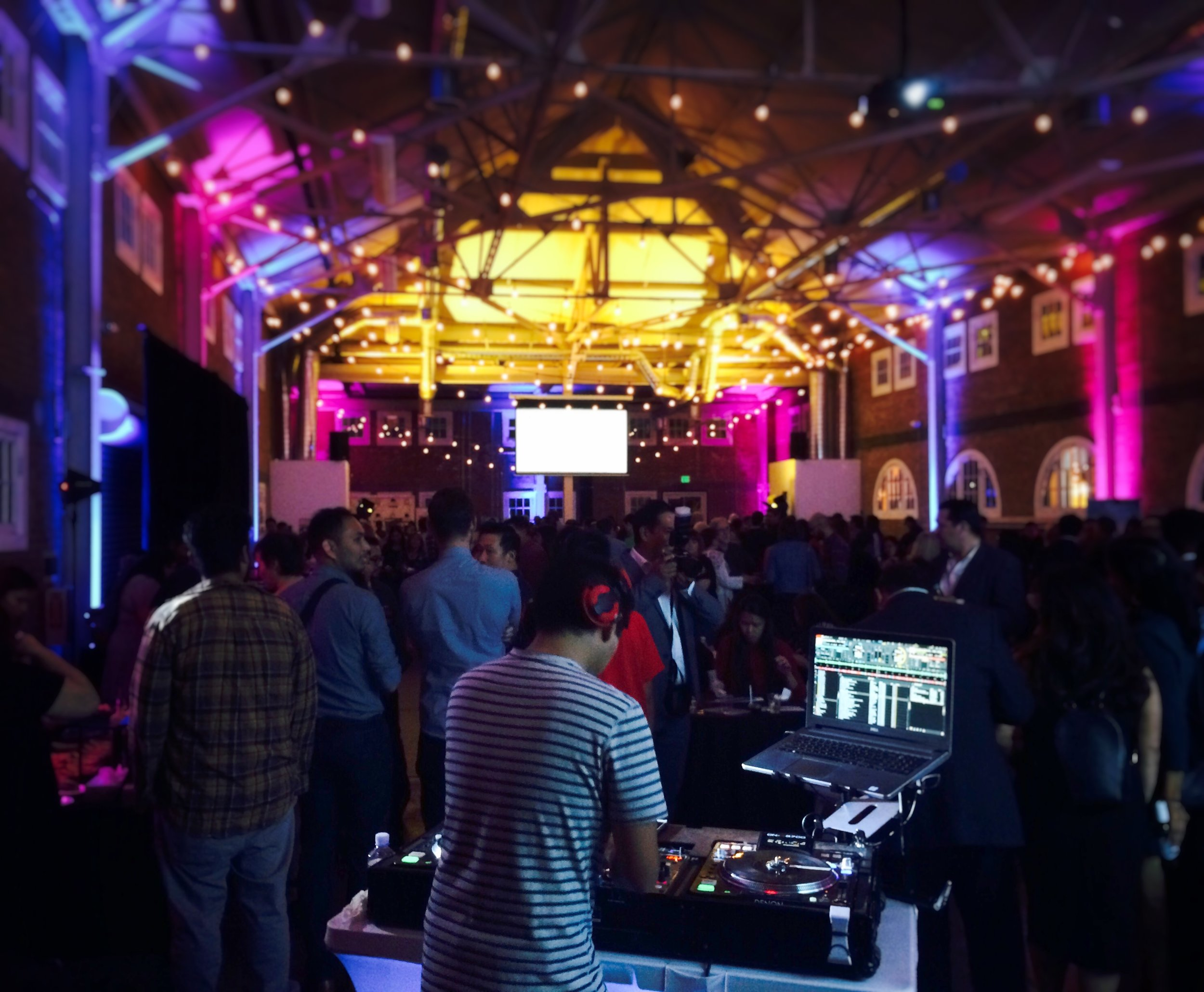 San Diego DJ Justin Kanoya spins music at an event at Brick, located in Liberty Station, San Diego. Uplighting and ceiling wash lighting transform this warehouse, brick building into a dynamic event space.