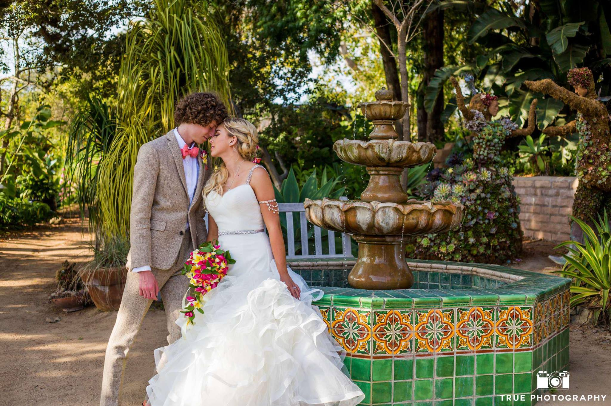Michelle and Cameron pose by a fountain after their wedding ceremony at the San Diego Botanic Garden.