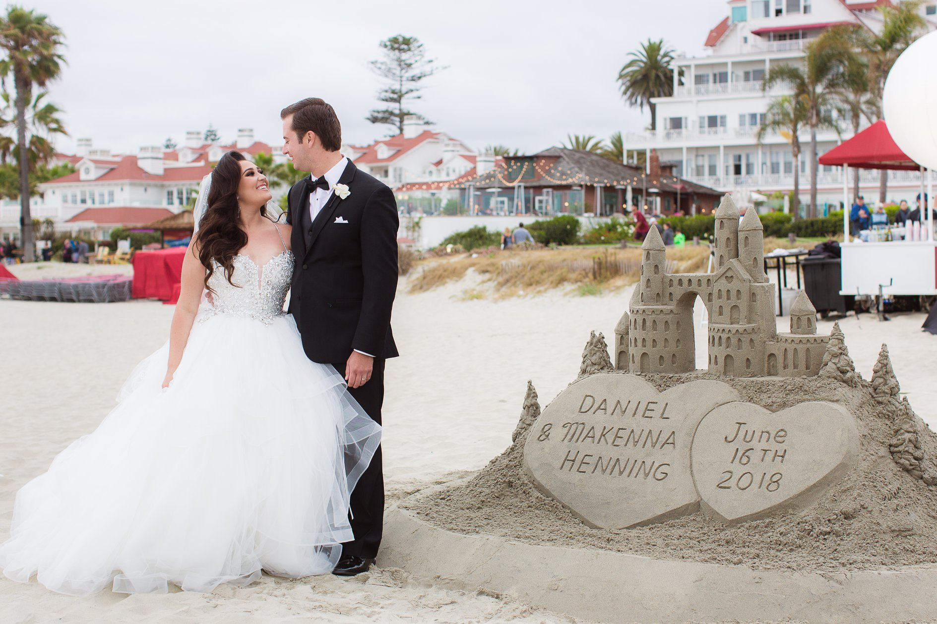 Makenna and Daniel pose on the beach next to a custom sandcastle after their wedding ceremony at the Hotel Del Coronado.