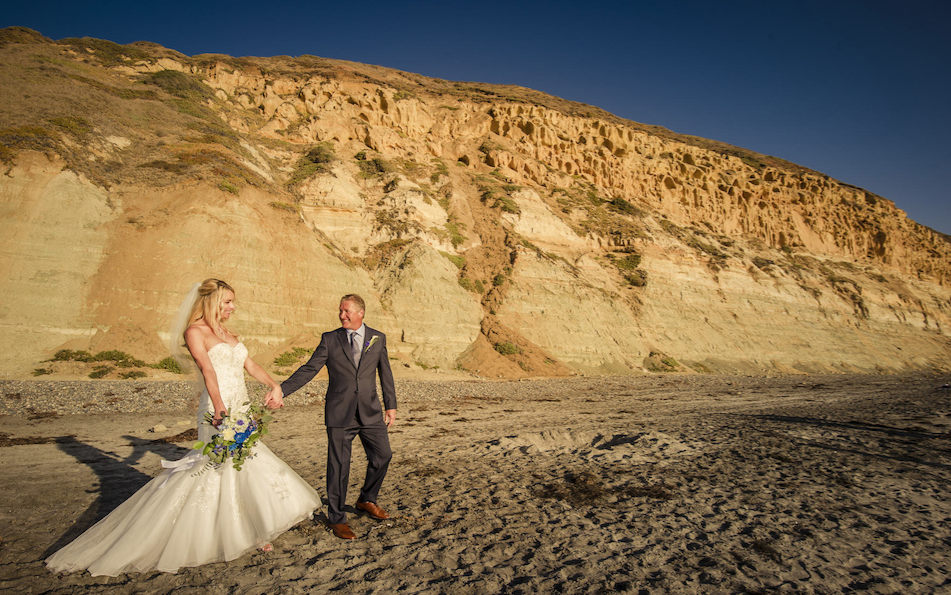 Richard and Stacy walk the sand after their wedding ceremony at the Hilton Torrey Pines.