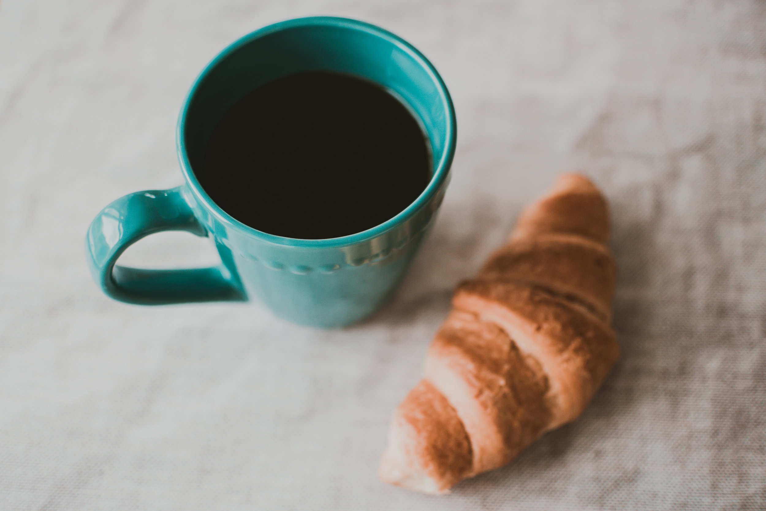 Canva - Teal Ceramic Mug Filled With Coffee Near Baked Bread.jpg