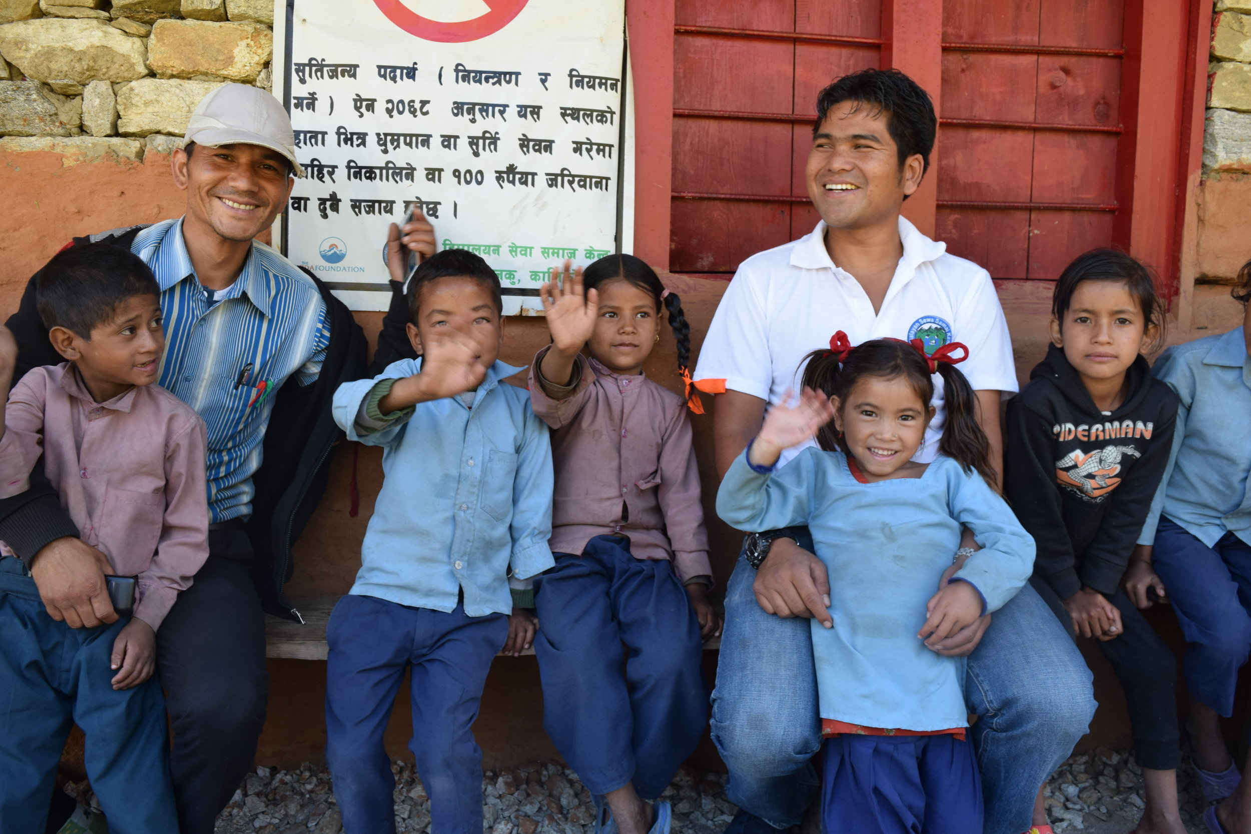 Karan sitting outside the Oda Foundation classroom with Head of Education, Purna Singh, and Rainbow class students.