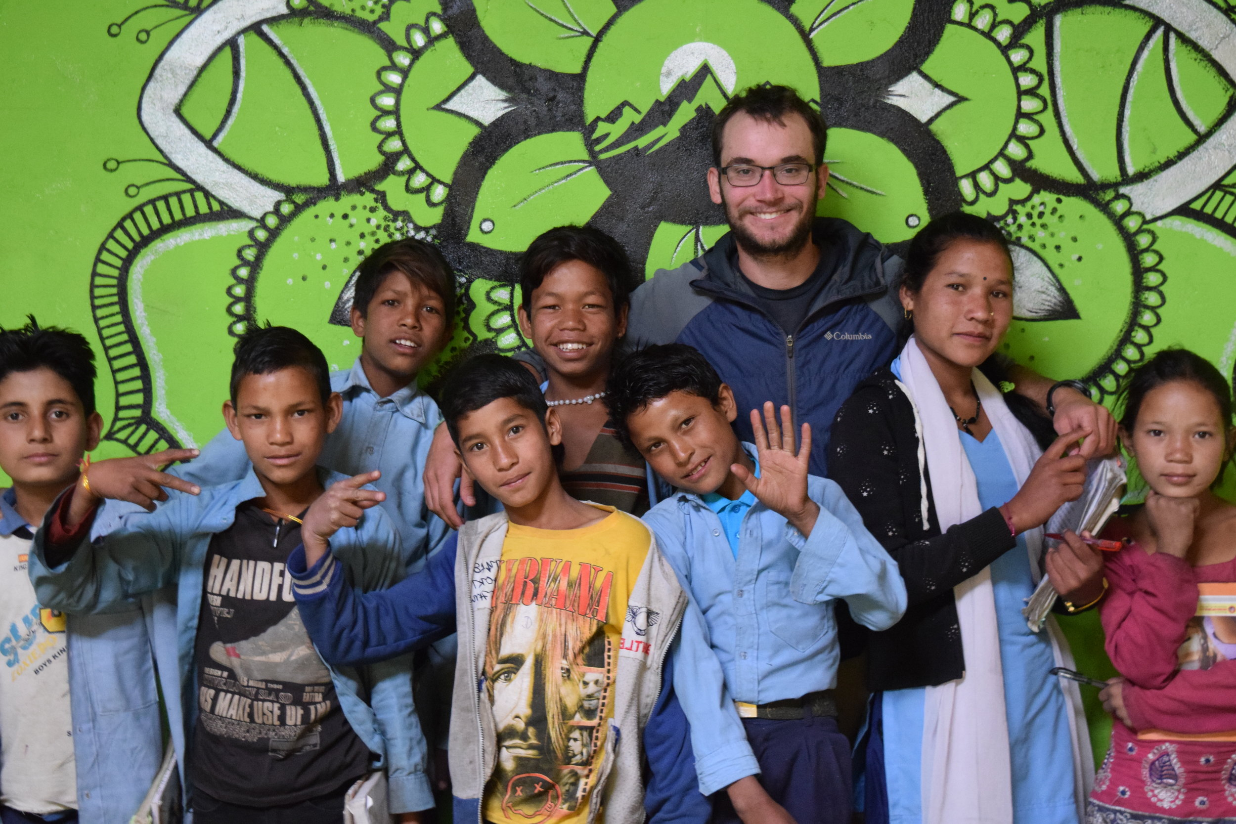 Aaron and his students in front of Taylor's mural at the government school