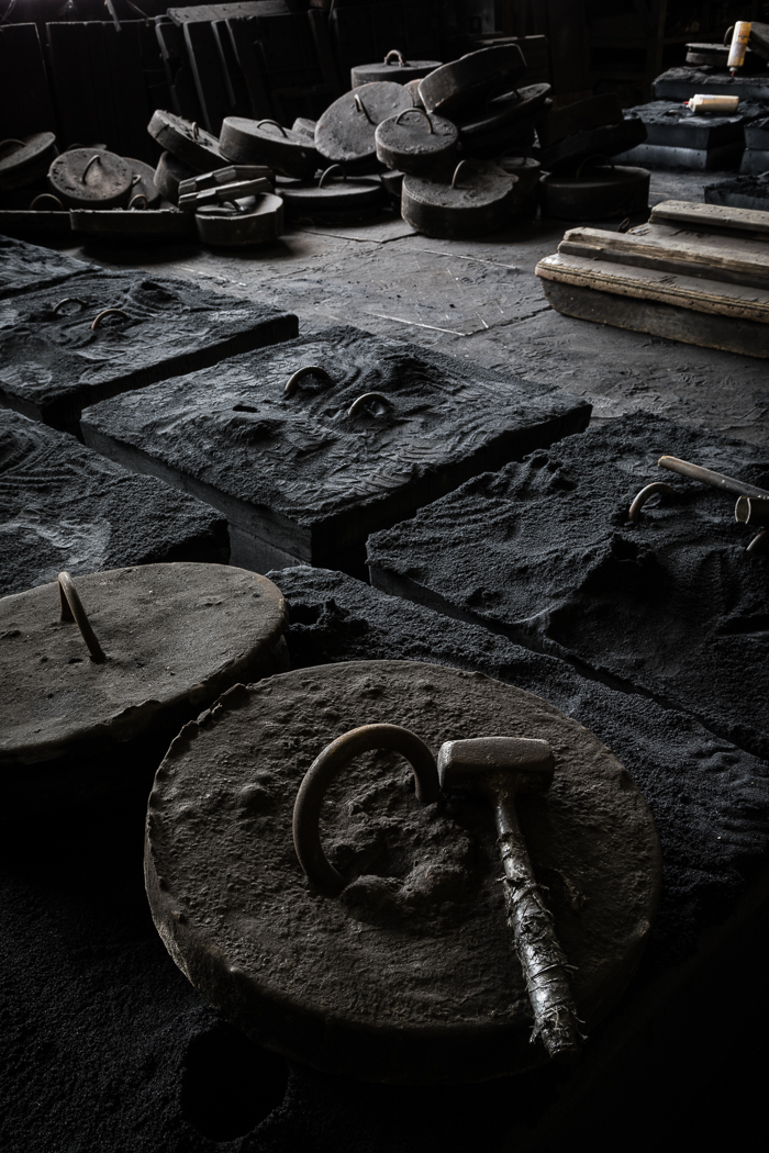 Metal Pieces and a Hammer on the Foundry Floor