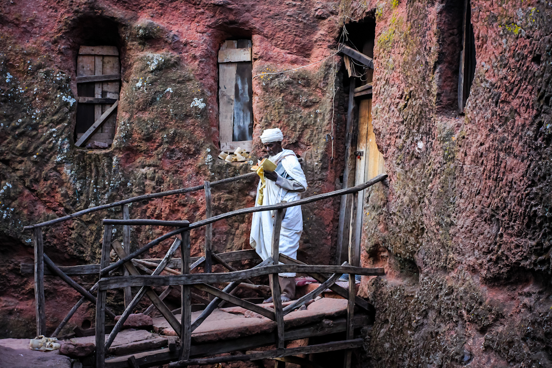 WORSHIPER studies holy scripture outside of a rock-hewn church in Lalibela