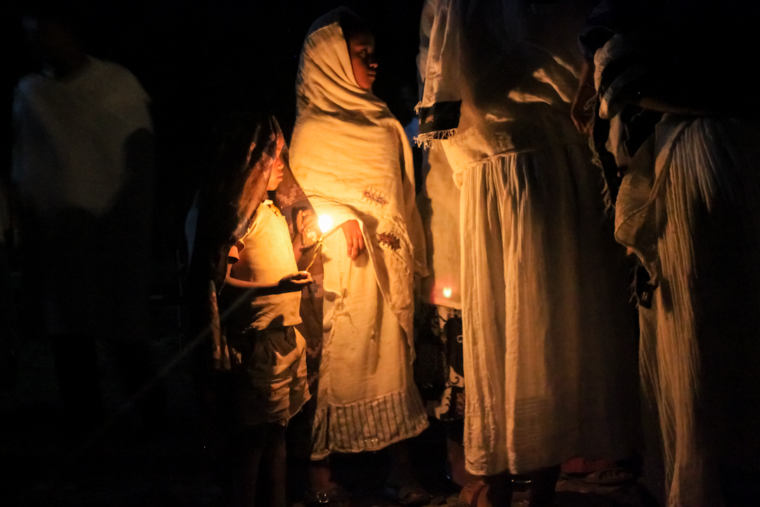 "WEARY WORSHIPERS guide their way home with beeswax candles from Debre Birhan Selassie Church in Gonder on the night of ""Fasika"""