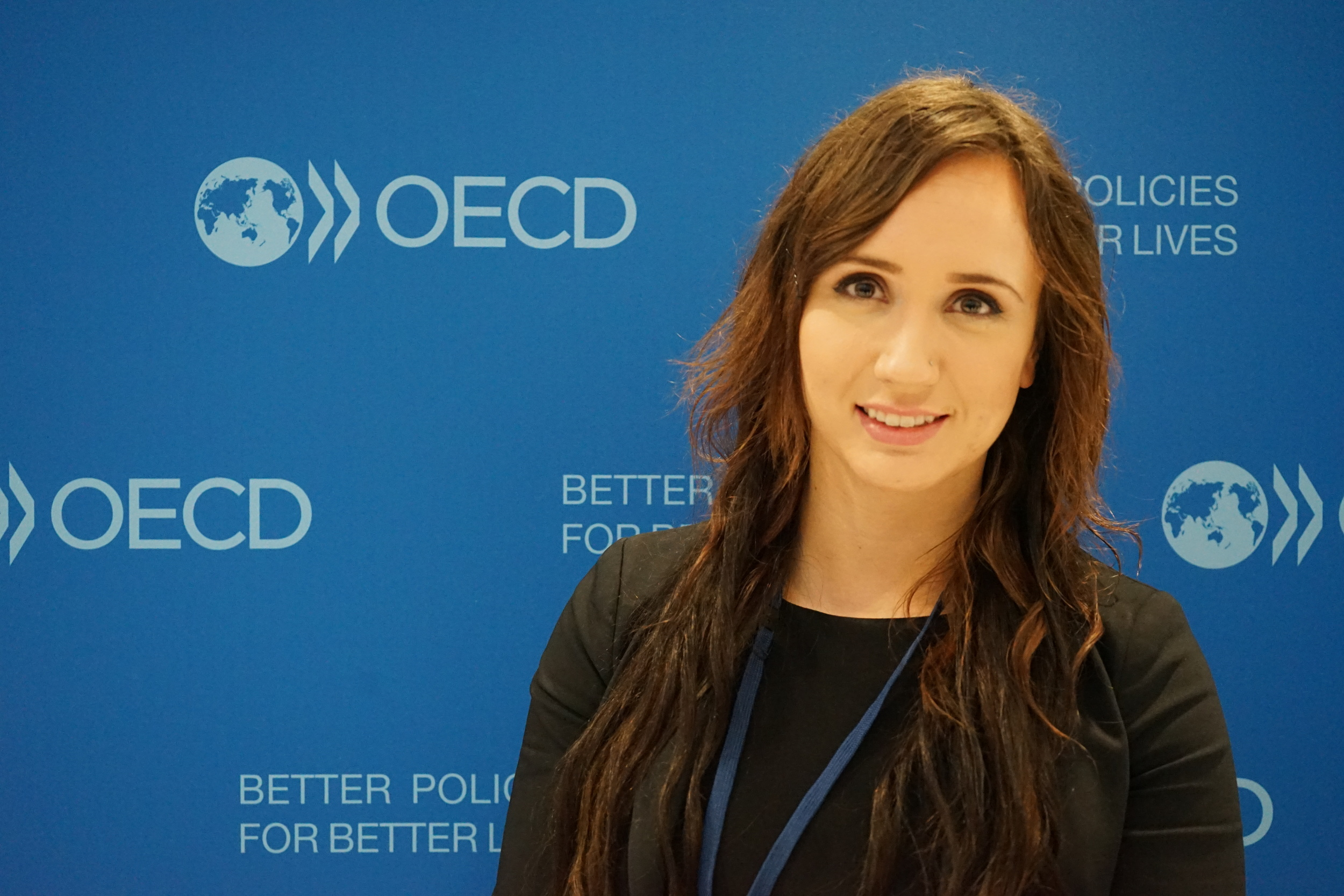 Gabrielle Bishop (Communications Coordinator) in front of OECD backdrop.JPG