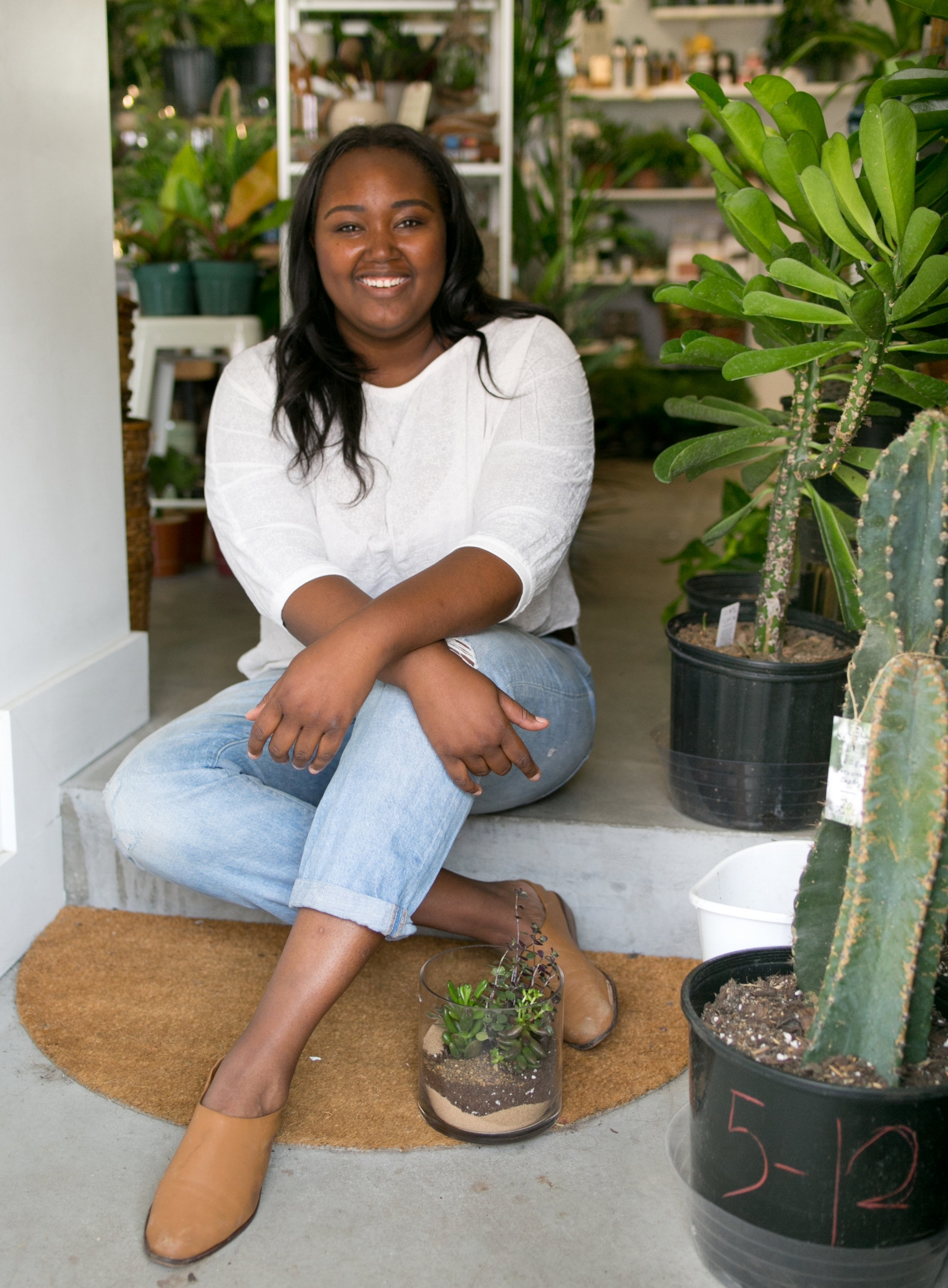 Megan George, owner of The ZEN Succulent, posing in the Durham storefront with one of her  handcrafted terrariums .