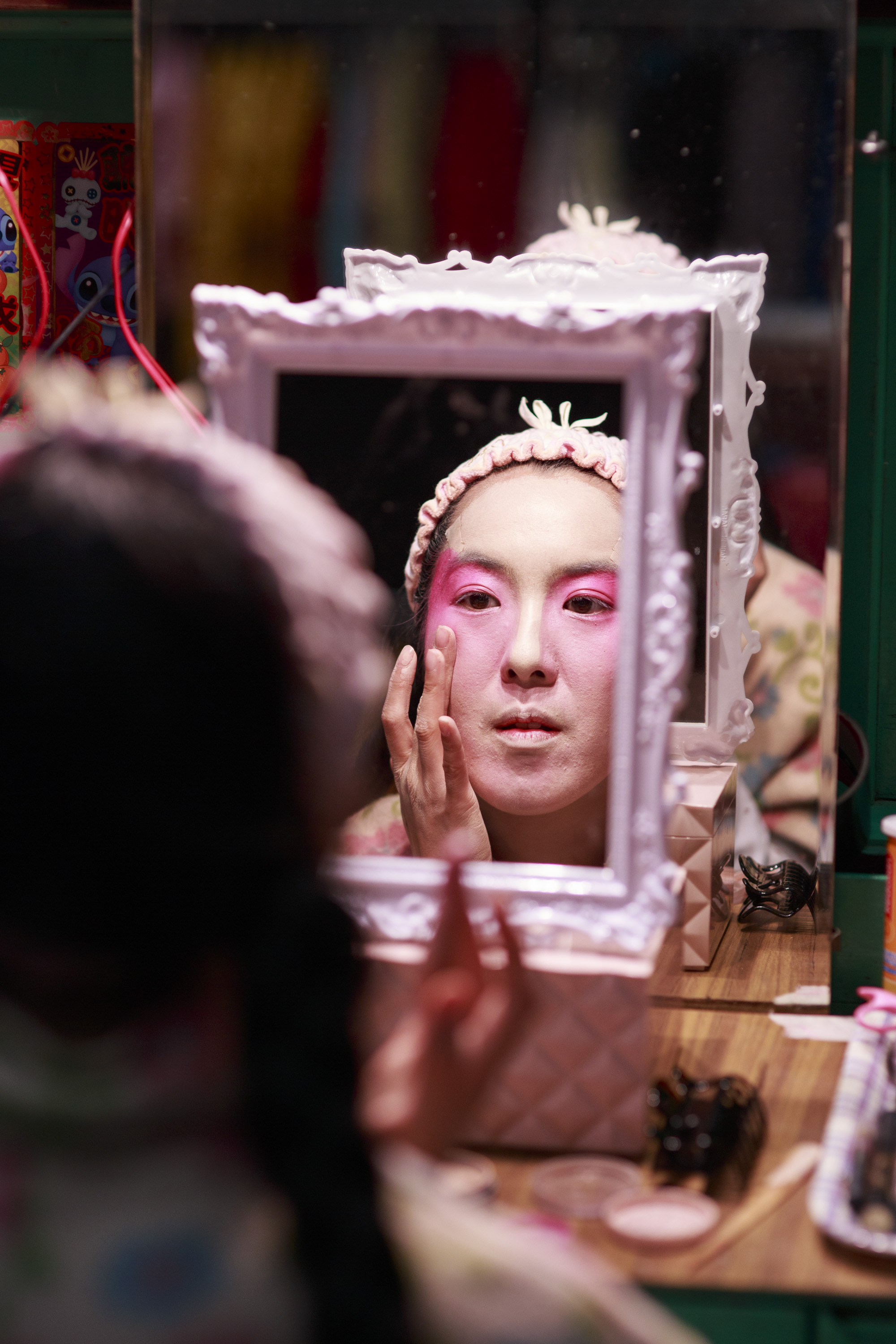Eliza Li, Chinese Opera singer seen here applying makeup for her performance