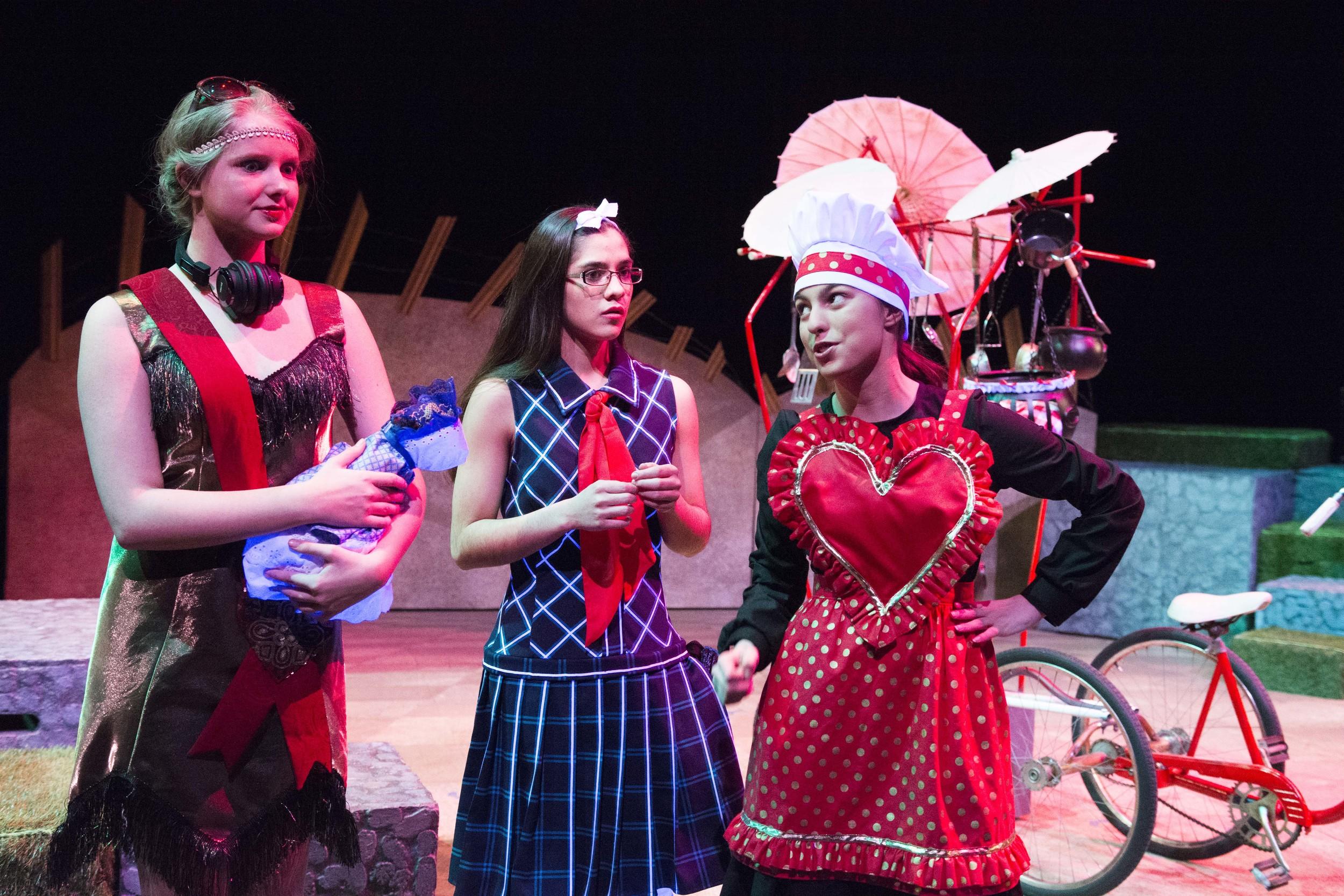 Callie Dochterman (The Dutchess, left), Carlie Campos Ott (Alice, center) and Aidan Hefner (Cook, right) meet along Alice's way through Wonderland.