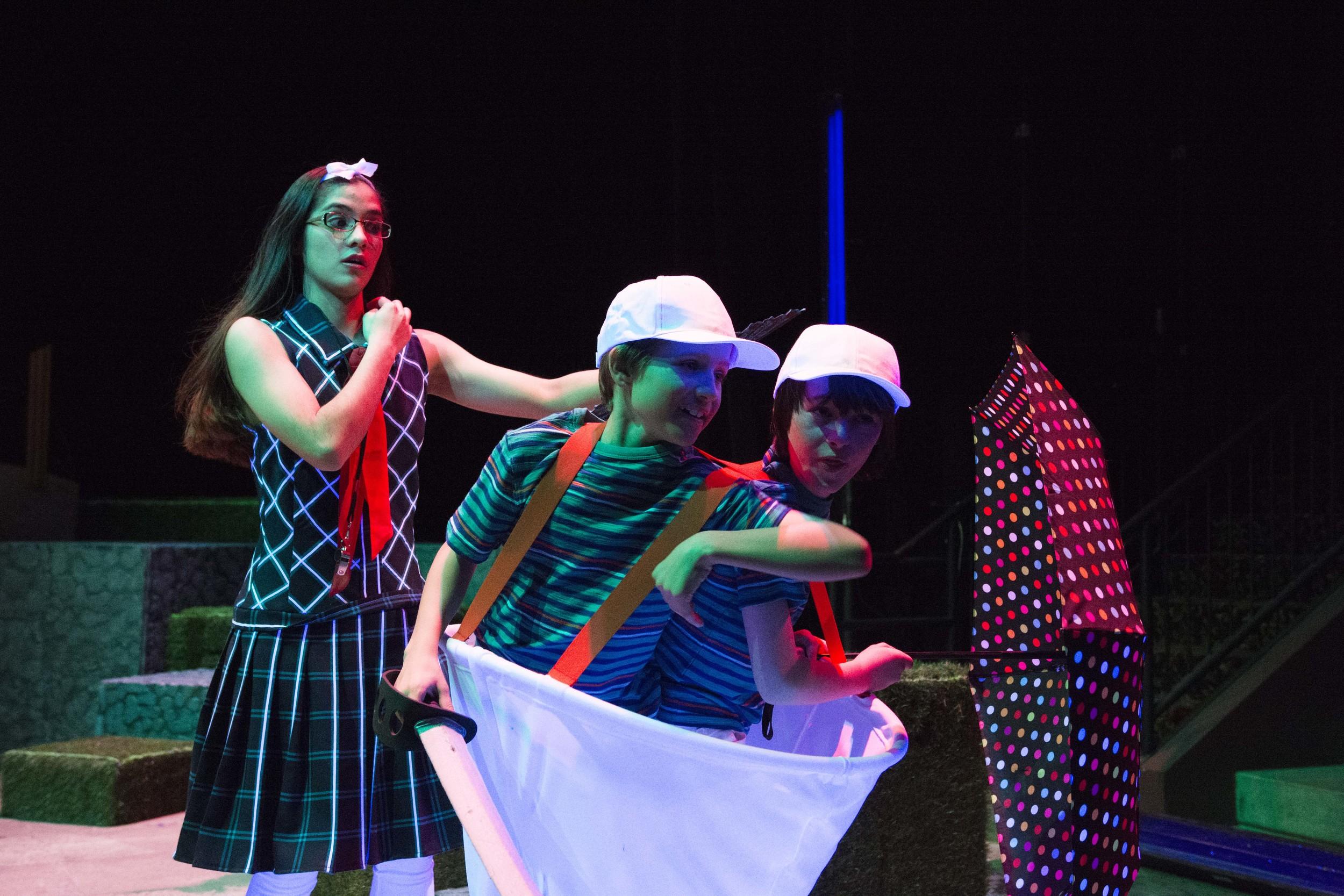 Carlie Campos Ott (Alice) encounters Tweedle Dum and Tweedle Dee (Jonah Neel, left, and Logan Schunemann, right)