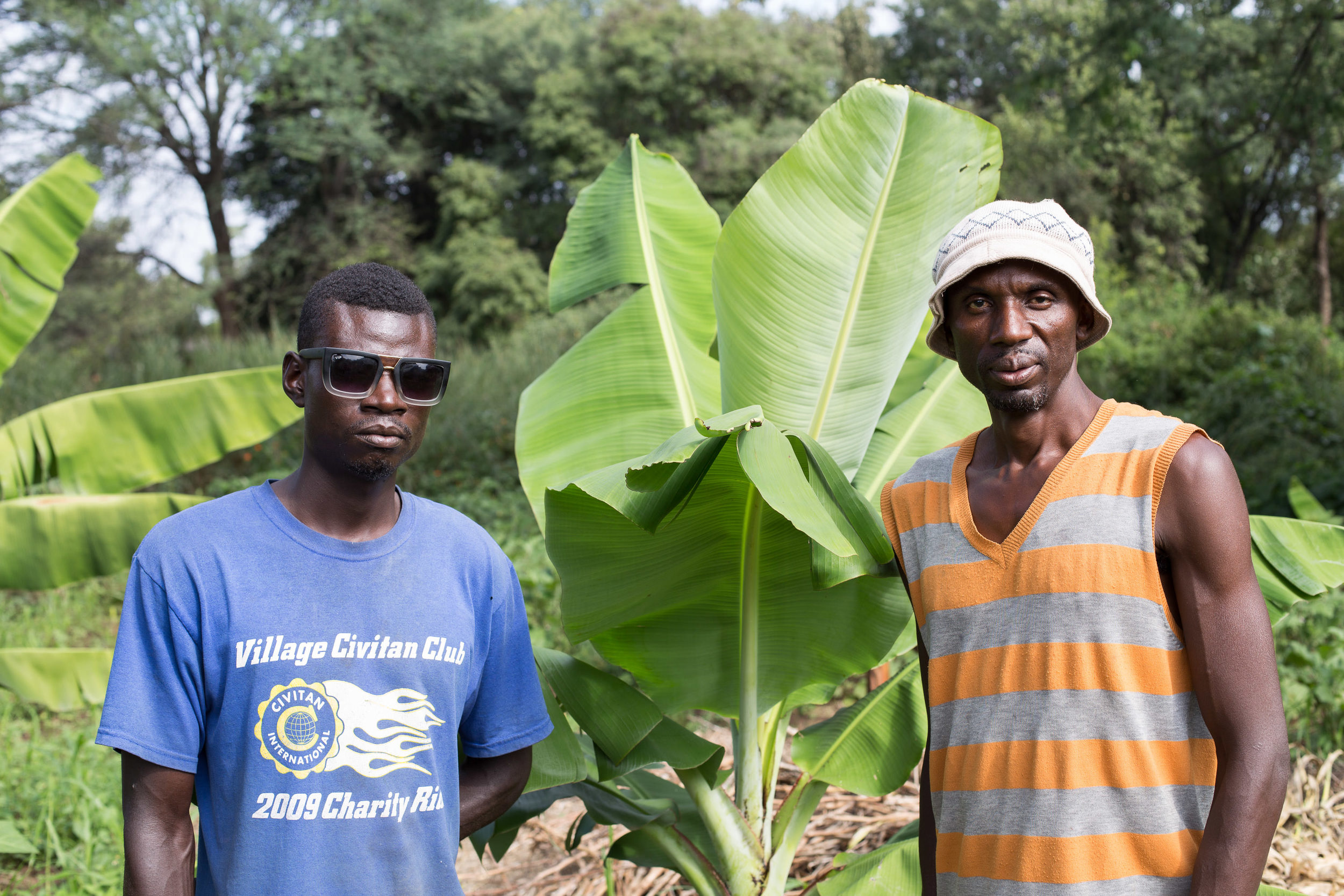 Robby (left) and his uncle in front of their new banana tree