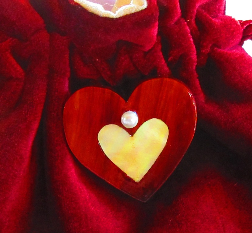 small Redheart wood heart with golden Mother-of-Pearl heart inlay and pearl-like bead to connect to red velvet bag