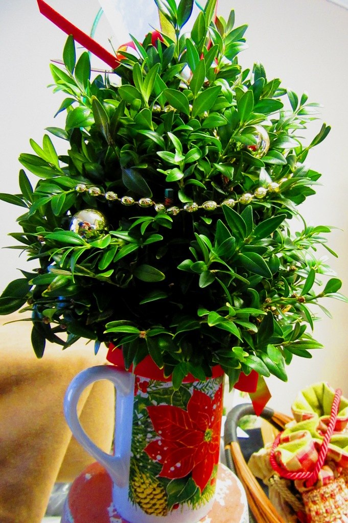 small boxwood arrangement in holiday mug with gold garland and balls