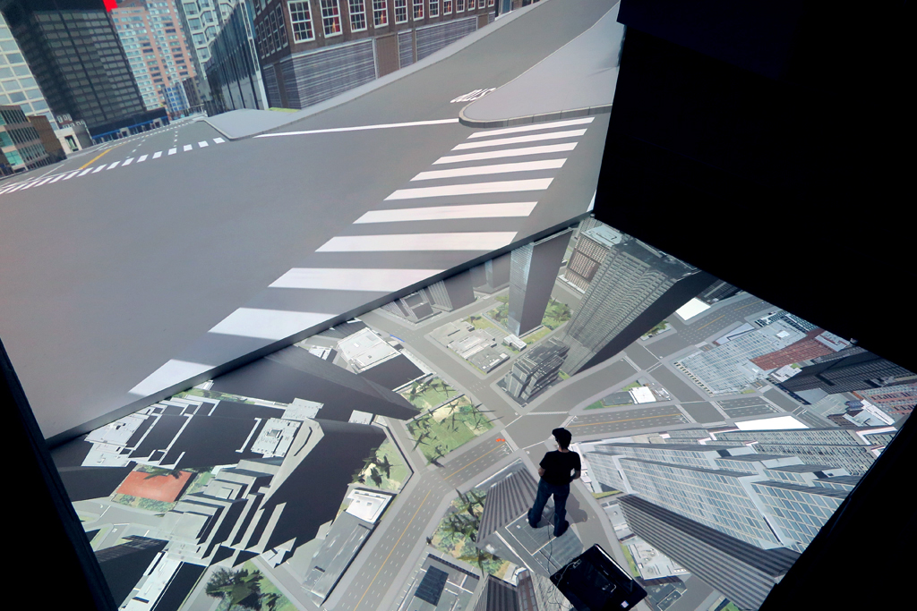 The simulation of an urban landscape within Deep Space 8K and a team member walking the virtual city. Source: TUMCREATE + Ars Electronica