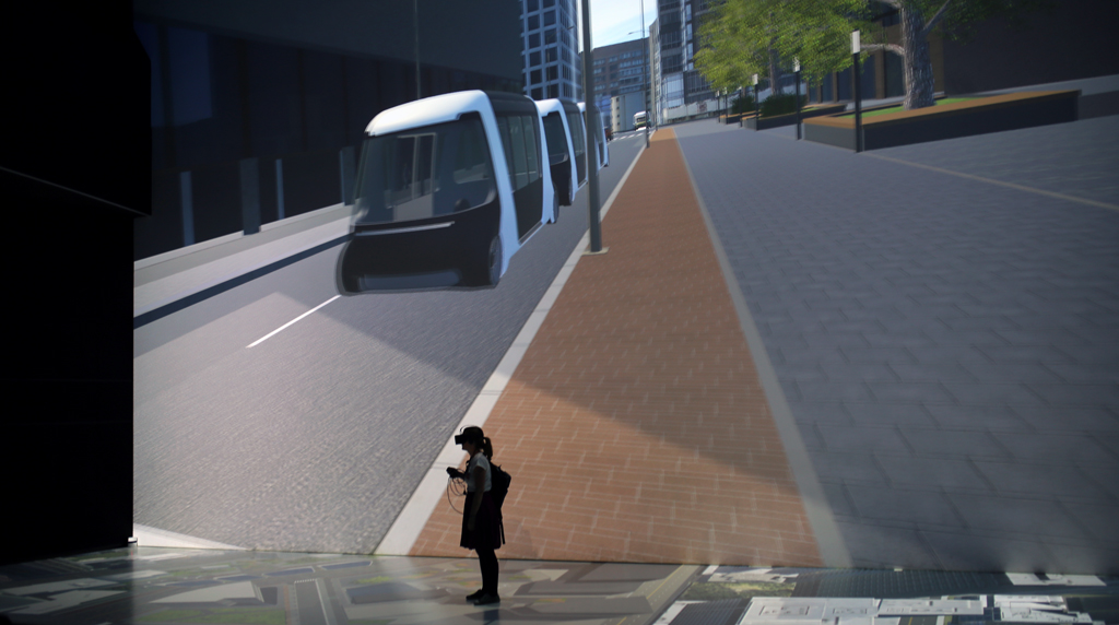 The perspective of the oculus rift wearer is displayed in 3D on the 16×9 metre display behind. A scenario with a human interacting with an AV on a pedestrian crossing. Source: TUMCREATE + Ars Electronica