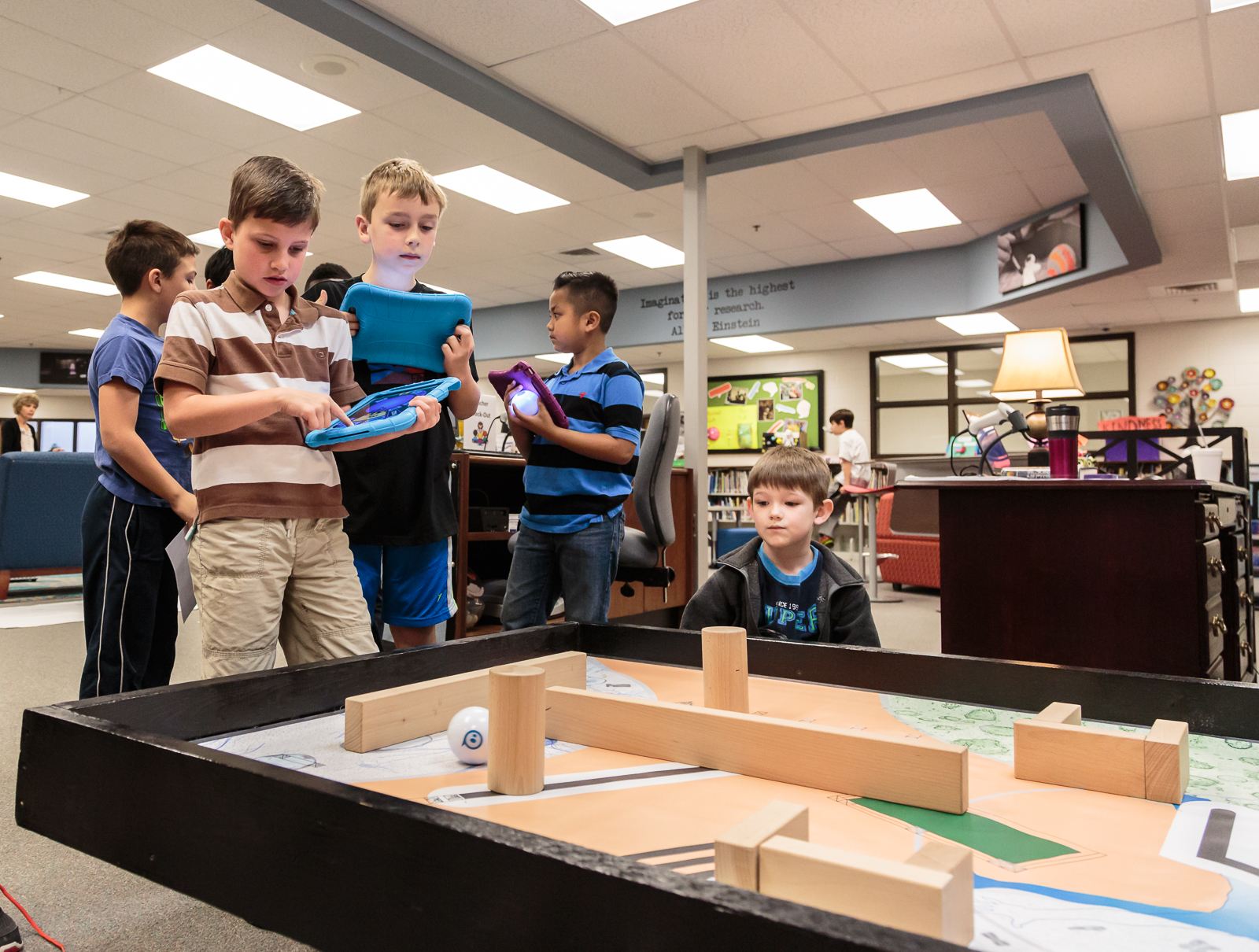 "A group of 2nd grade students took turns using a tablet acting as a remote control to guide a motorized robot ball through a maze of wooden blocks. ""The speed and the power made it pretty hard,"" says  Cody ."