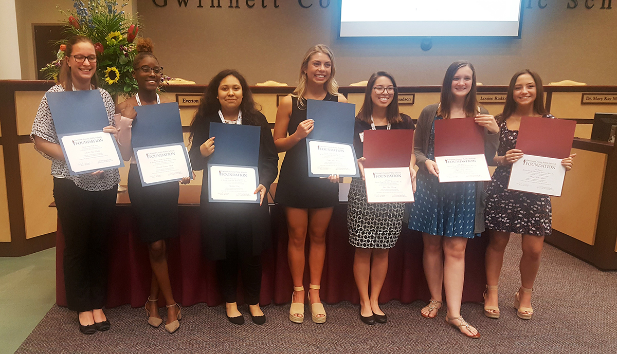 Students show scholarships for future educators.