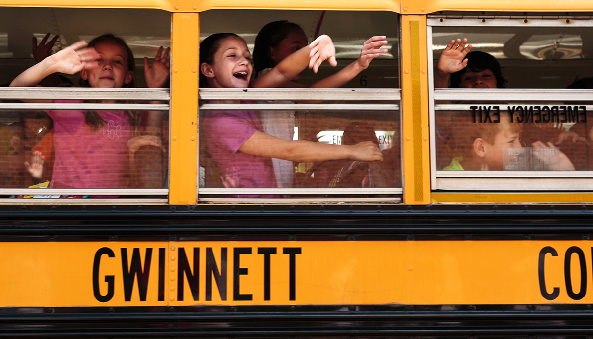 Children wave from school bus