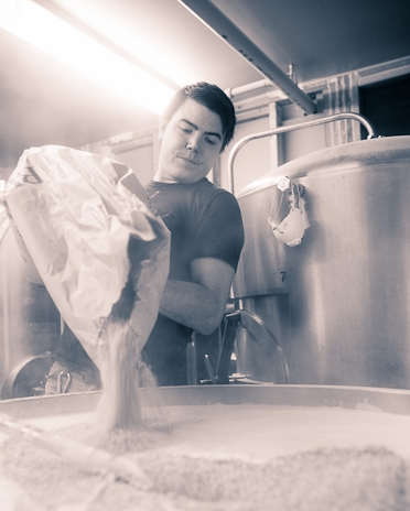 Jean pouring grain into the mash tun.