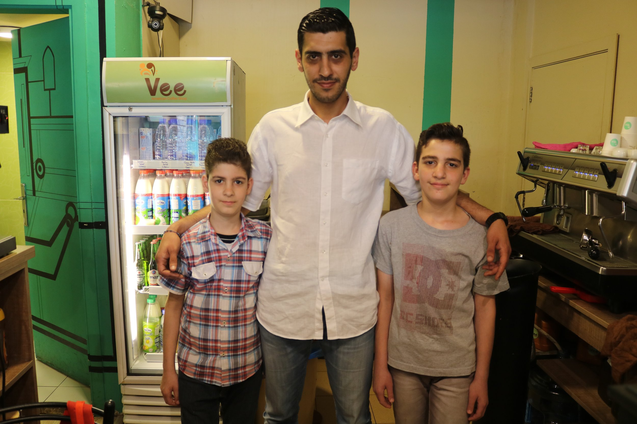 Fadi (left) and Farah (right) work at a cafe in northern Lebanon. Their boss, Samir (middle), hired them to get the boys to talk again. They've been quiet since witnessing ISIS kidnap their sister and shoot their mother.