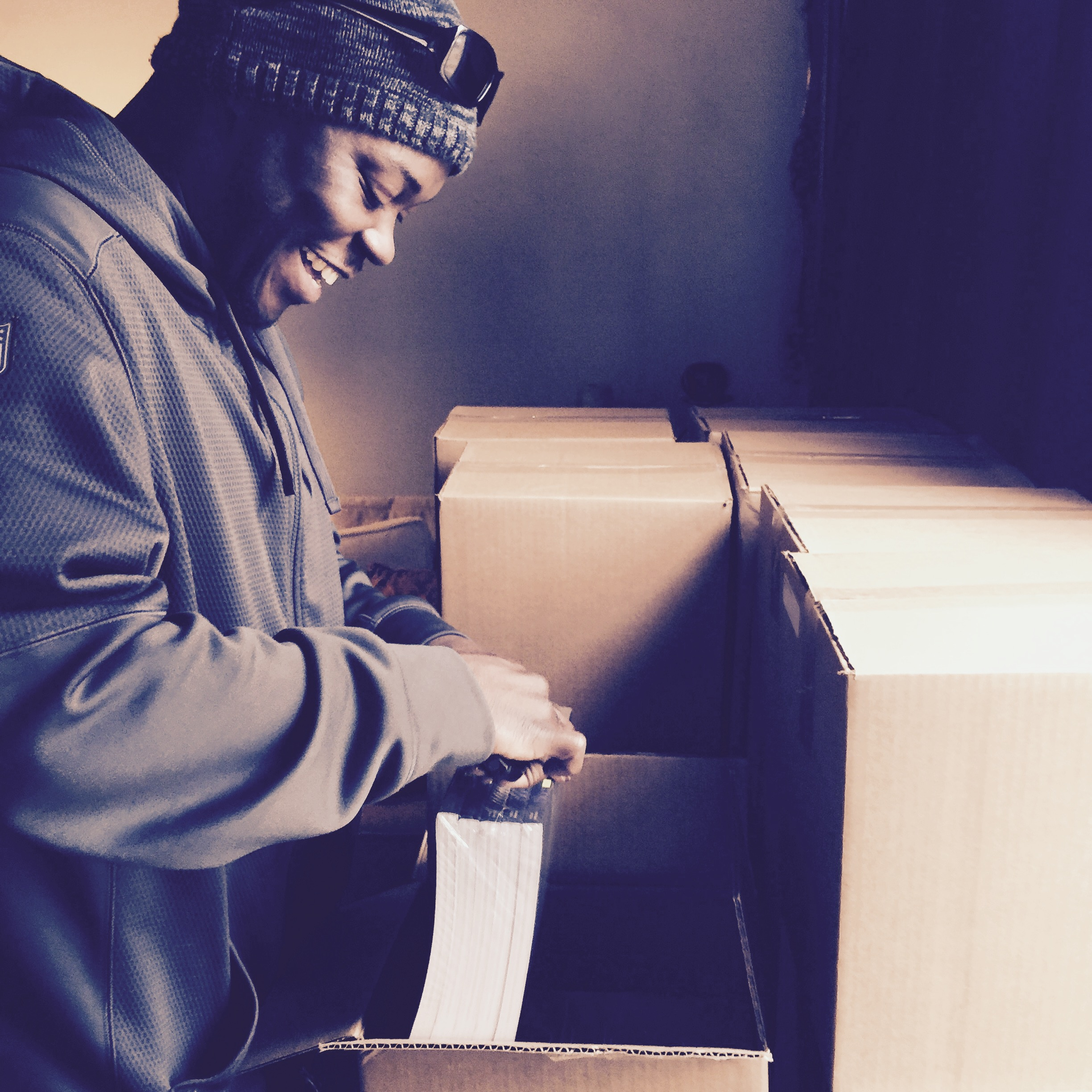 Kofi unpacking the first shipment of books because I was too excited