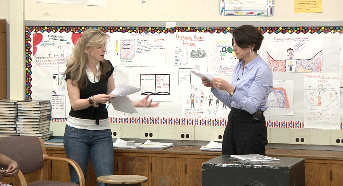 A theater teacher and facilitator demonstrate a scene for their class.