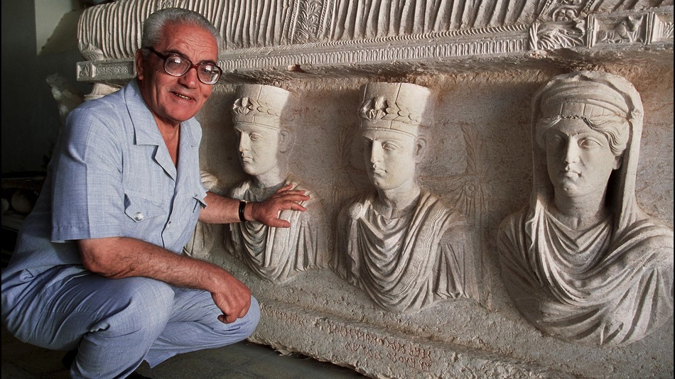 Khaled al-Asaad poses in front of a sarcophagus in Palmyra, Syria, 2002. Photo by Marc Deville.