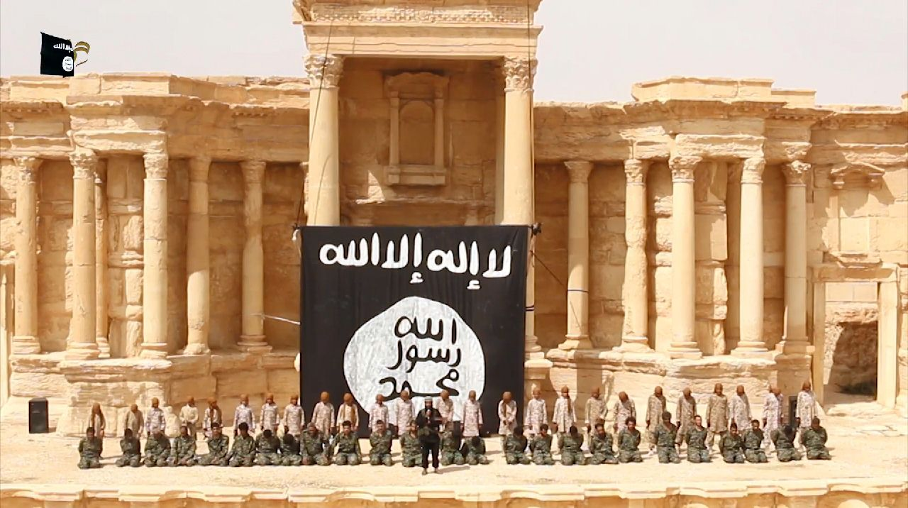 25 Syrian government soldiers kneel in the ancient amphitheatre in the city of Palmyra ahead of being executed by children.Photo by Welayat Homs.