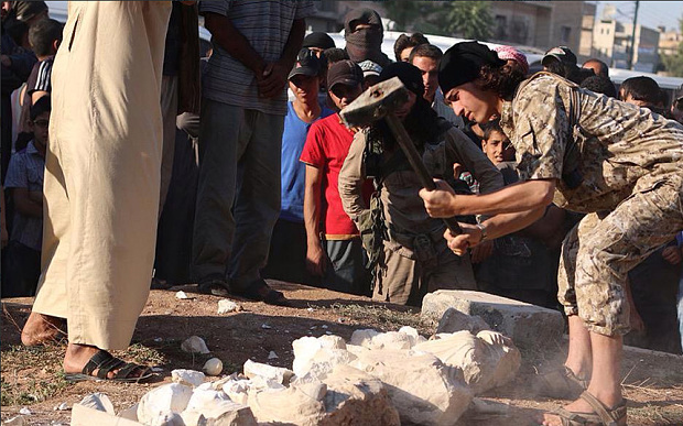 An Islamic State militant destroys ancient artifacts in the ancient Syrian city of Palmyra, Syria on July 2, 2015.