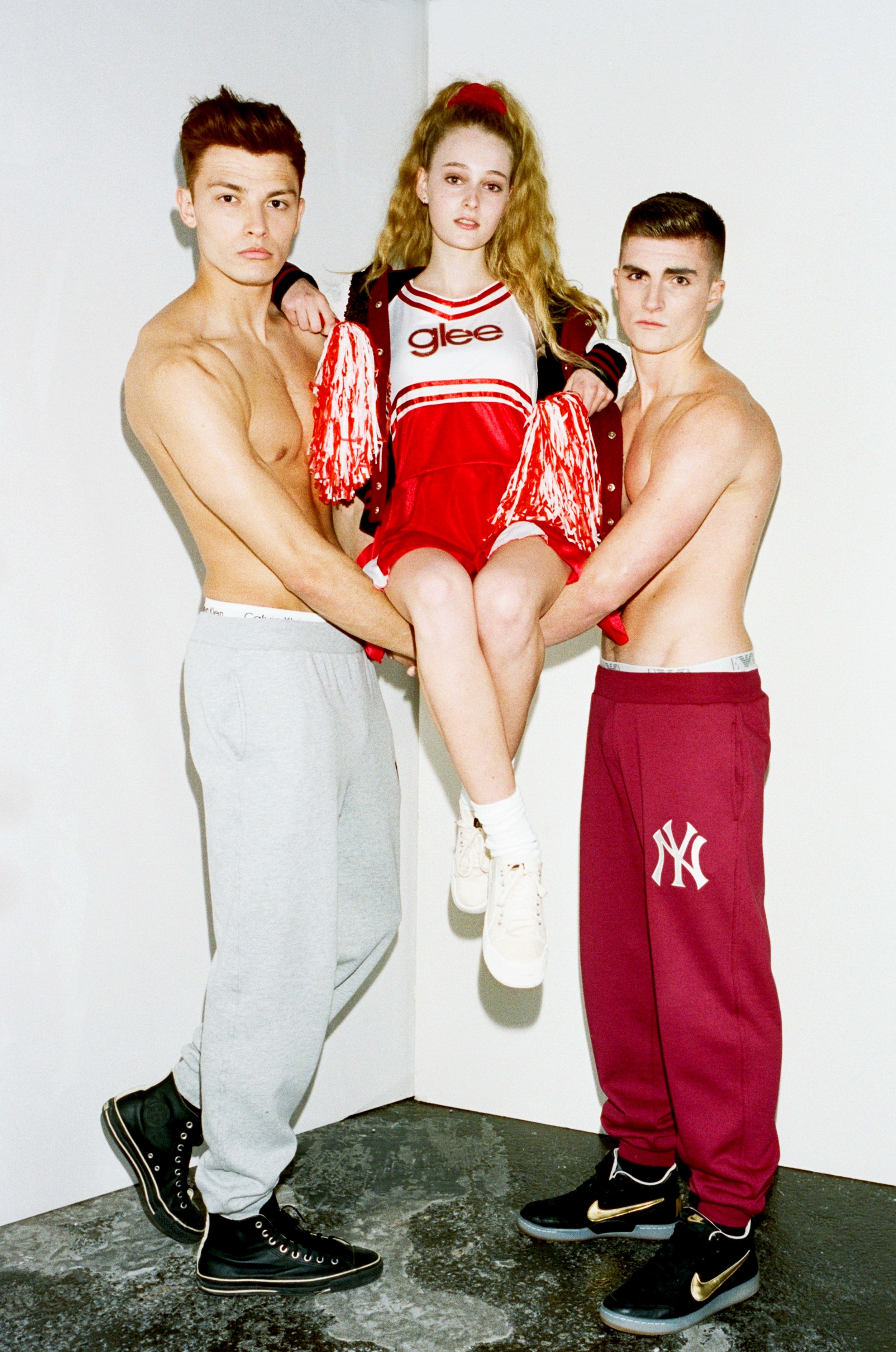 Nick wears Grey Jogging Bottoms by Majestic, Trainers by Converse, Anna wears Cheerleader Costume - Stylist's Own, Sequin Varsity Jacket by Ashish, Trainers from Beyond Retro, Tyler wears Red Jogging Bottoms by Majestic, Trainers by Nike