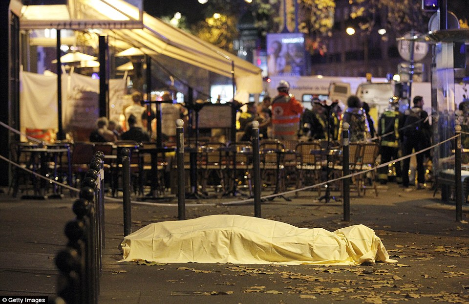 A victim's body lies covered on Boulevard des Filles du Calvaire, close to the Bataclan theatre. Photo by AP Images