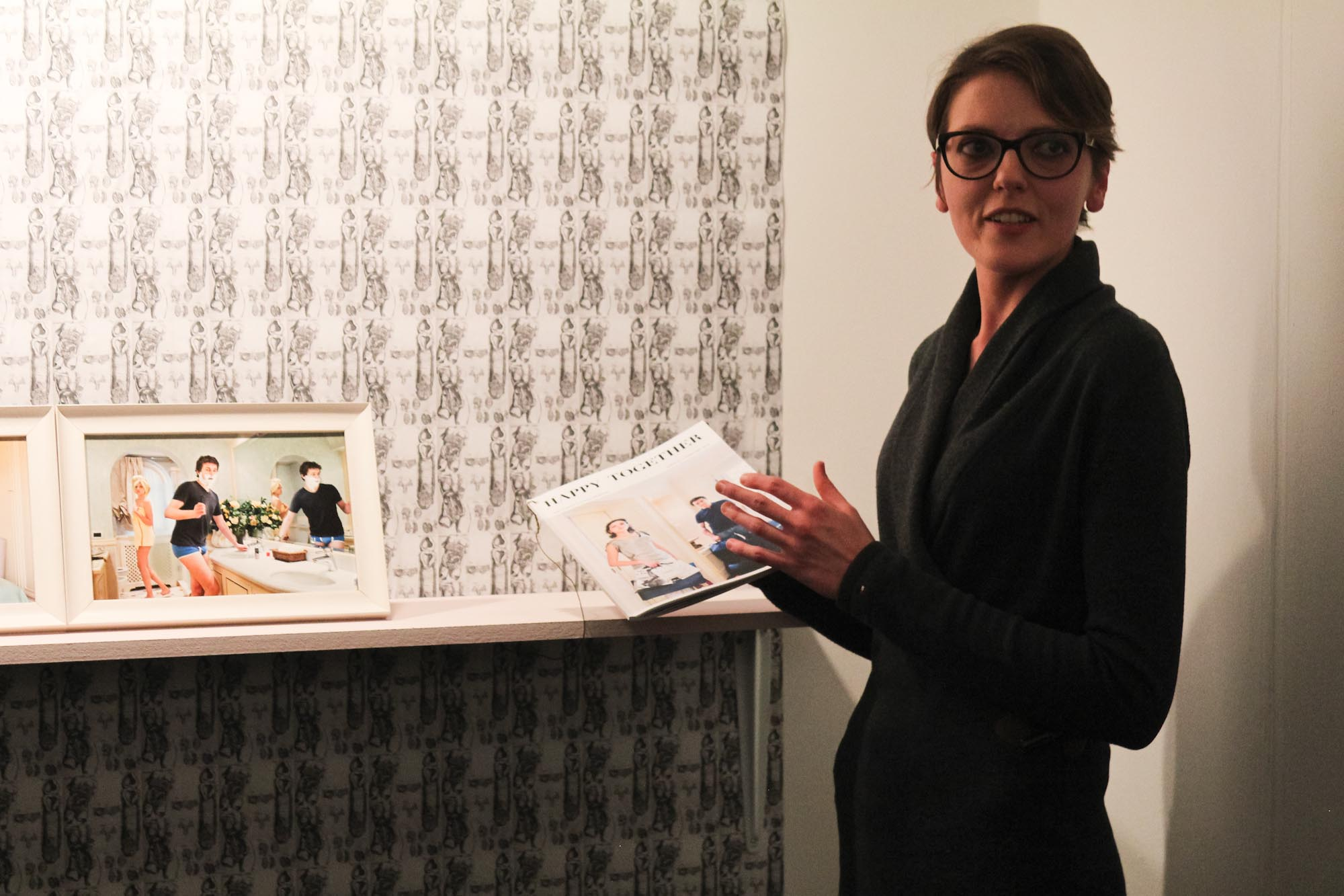 Francesca Catastini holding the magazine from of her series 'Happy Together' (2010), with framed prints from it on the shelf, and a repeating print of female genitalia as the wallpaper.