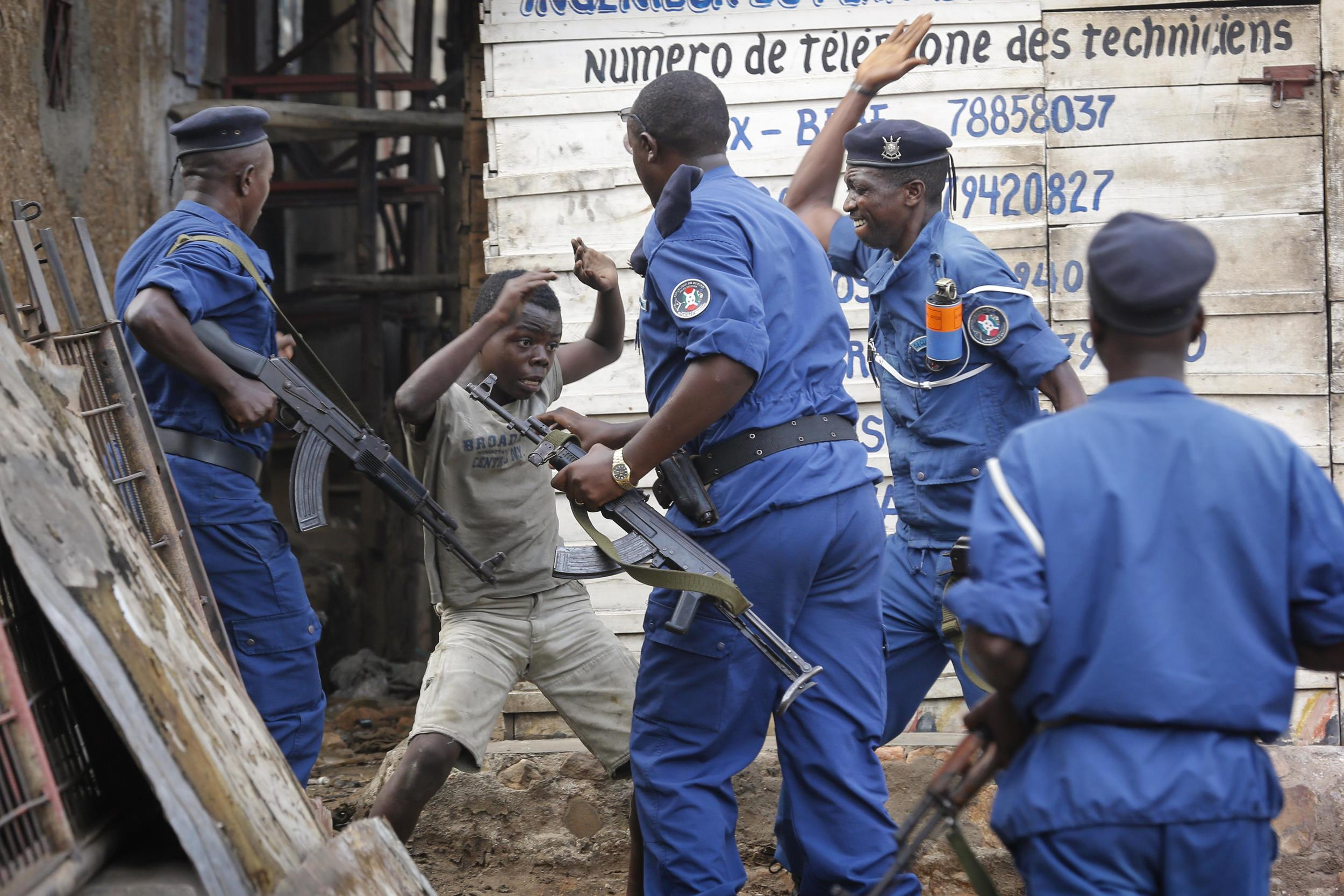 A young Burundian boy beaten by armed police officers during protest in Bujumbura over president's third term, 2015 photo by Dai Kurokawa / EPA