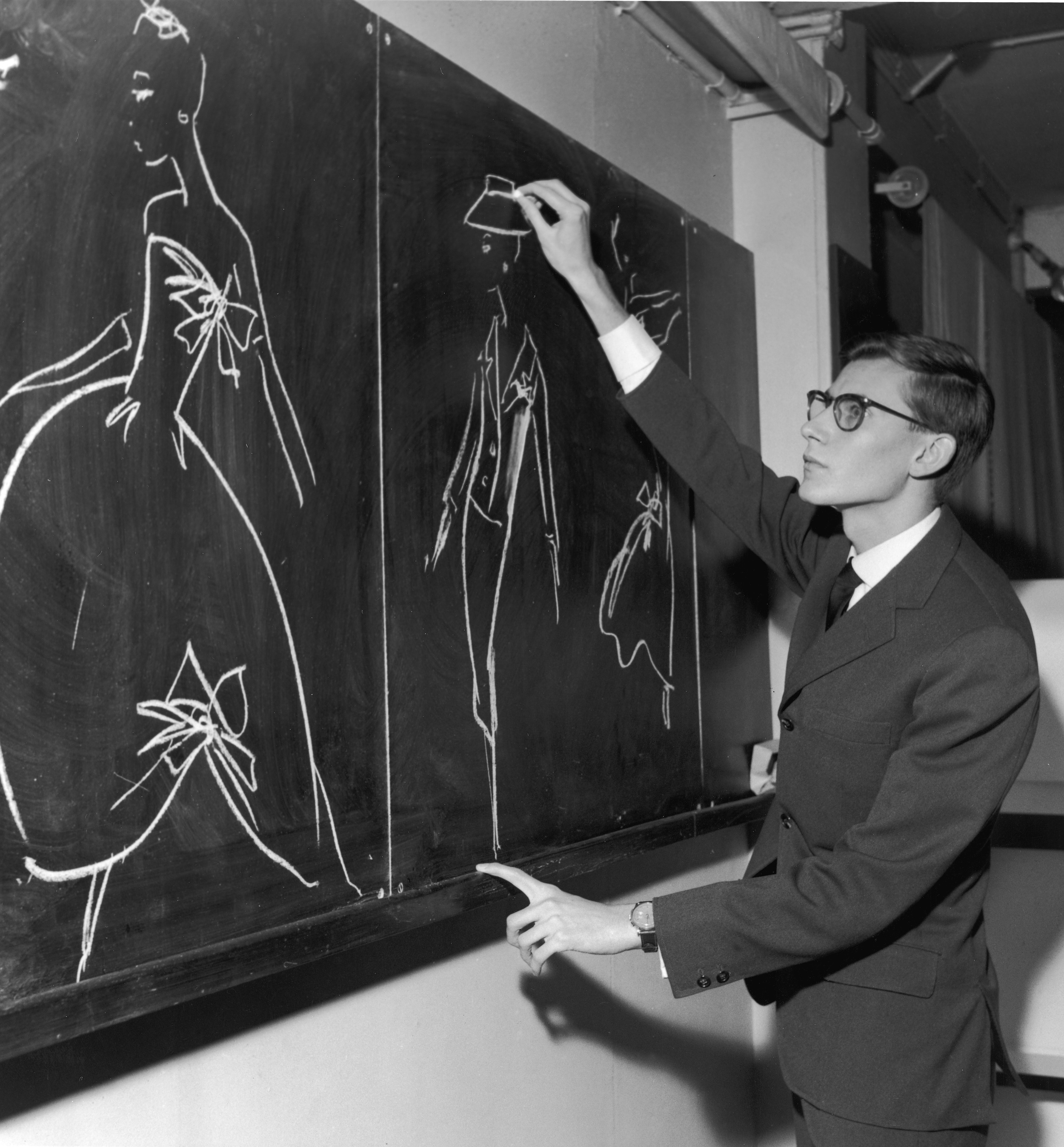 Yves Saint-Laurent using chalk to sketch fashion designs for Christian Dior. Paris, France 1957