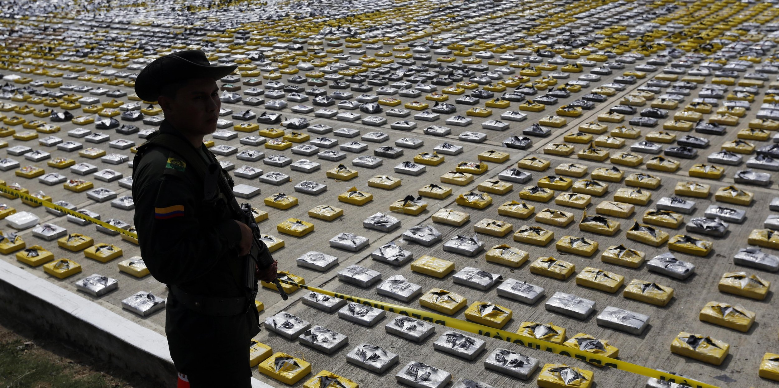 An armed police officer stands guarding packages of seized cocaine in Colombia, 2015