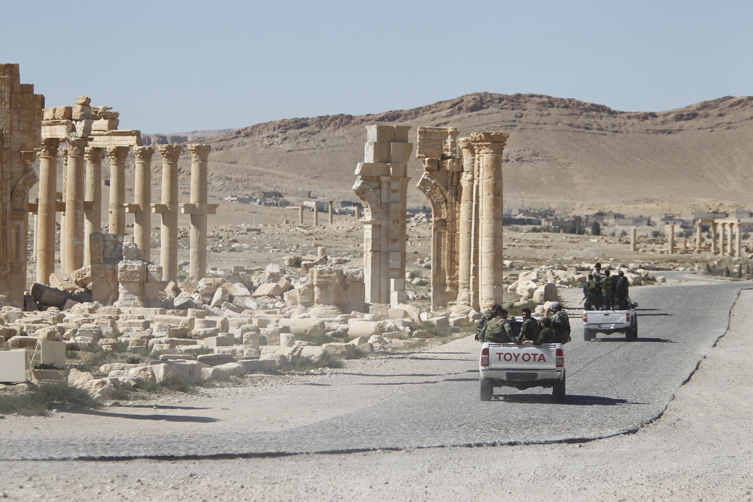 Syrian army soldiers drive past the ruins of the Arch of Triumph in the historic city of Palmyra, in Homs Governorate, Syria April 1, 2016. Photo by Reuters/Omar Sanadiki.