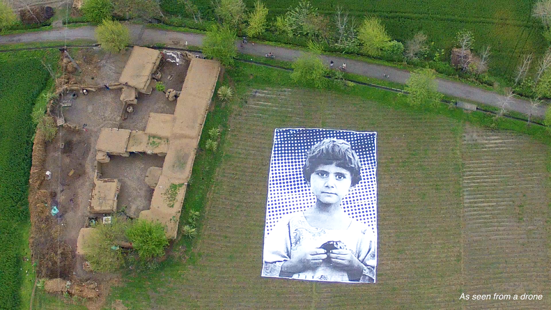 A poster bearing the image of a Pakistani girl whose parents were killed in a drone strike, lies in a field at an undisclosed location in the northwestern Khyber-Pakhtunkhwa province. Photo source: # NotABugSplat /AFP/Getty Images.