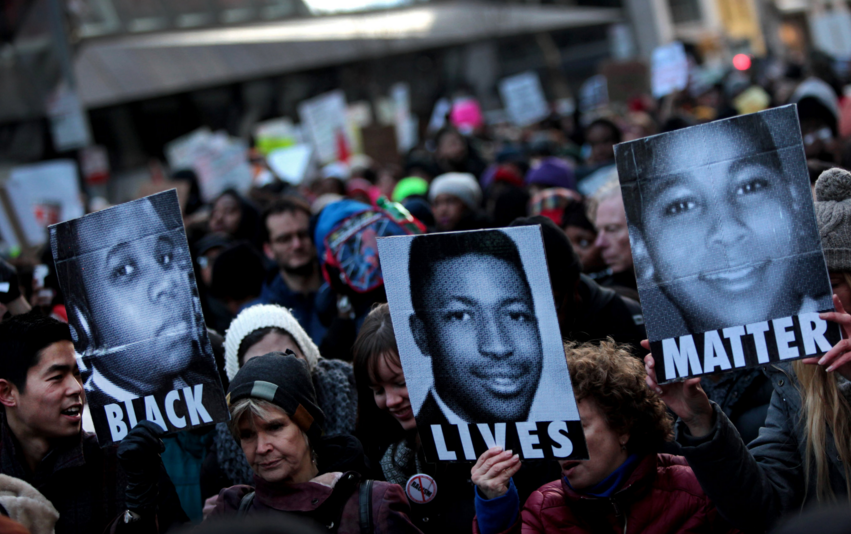 Protesters held images of Michael Brown, Eric Garner and Tamir Rice. Photo by Yana Paskova for  The New York Times .
