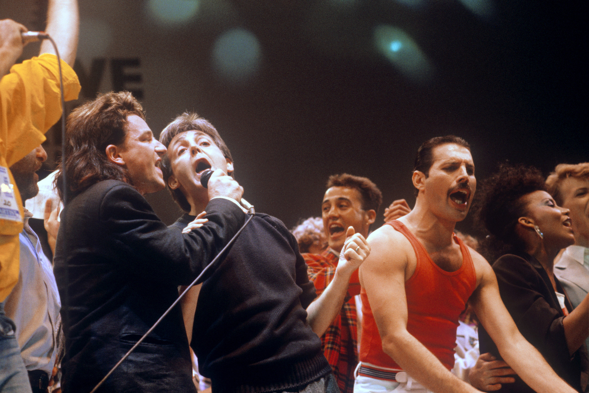 Bono, Paul McCartney, and Freddie Mercury performing at Live Aid concert, 1985.