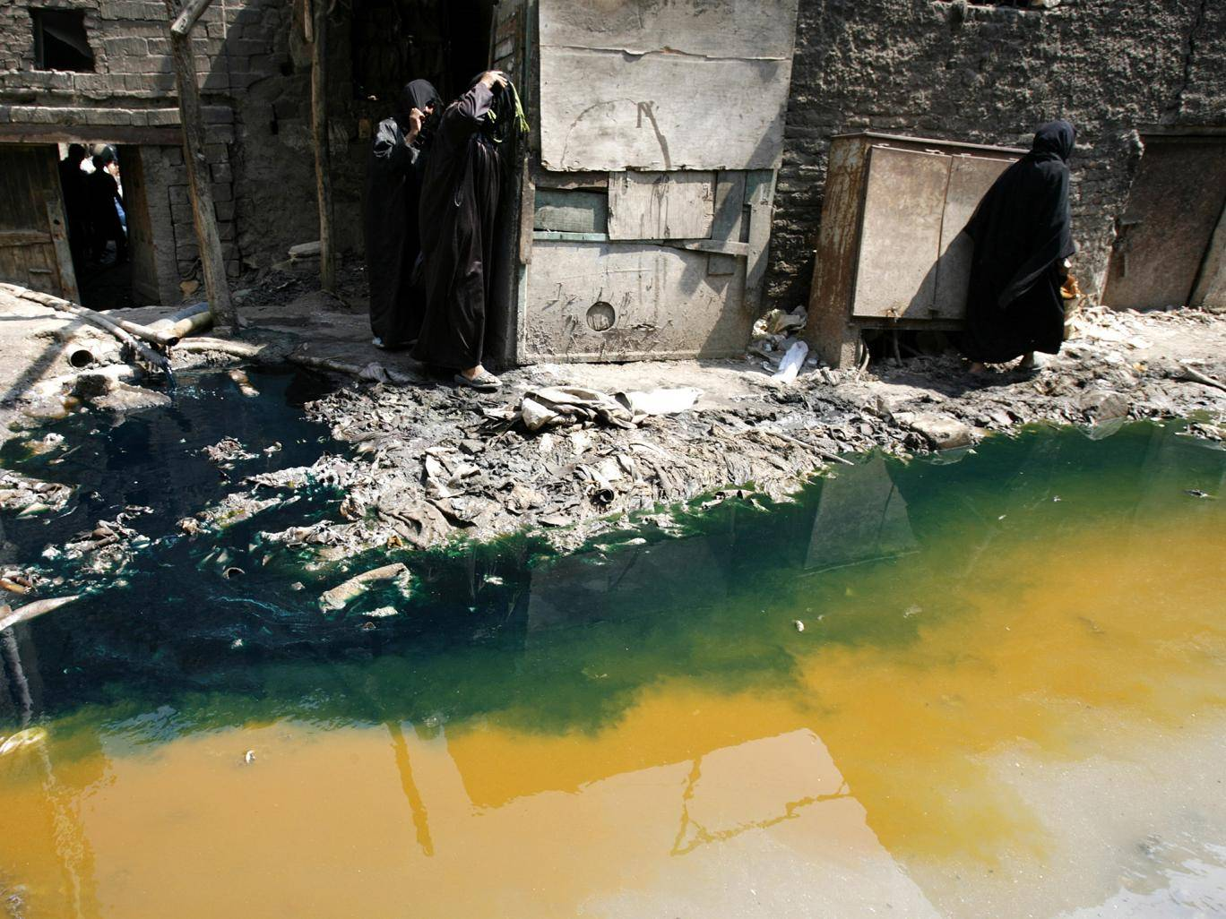 Women walk past tannery wastewater that is being pumped from a factory straight into the street, in Cairo's Ain el-Sirra district. Photo source:Reuters.